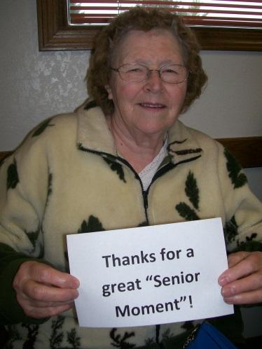 "Elderly woman holding a sign that says ""Thanks for a great Senior Moment""."