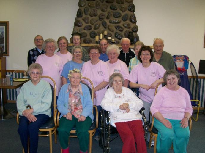 16 elderly individuals posing for a picture after a Helping Hands Outreach sponsored class.